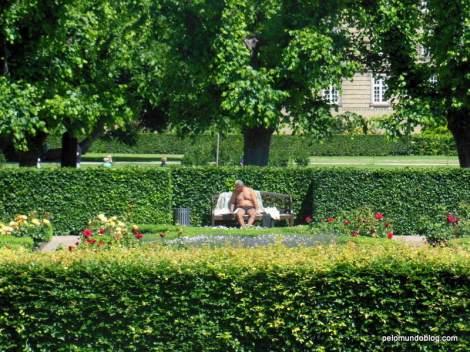 Pessoa bem à vontade, pegando um solzinho no jardim do castelo de Rosenborg.