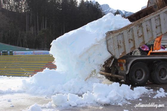 Caminhão descarregando a neve perto da pista.