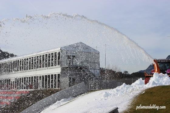 Outra máquina vinha e jogava a neve para espalhar na pista.