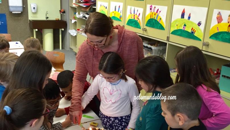 Cortando o bolo junto com a professora e os colegas.